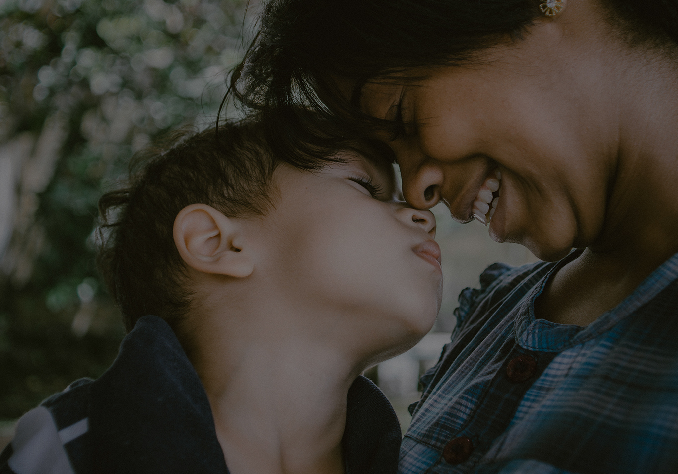 Close up of woman and child touching noses and smiling with closed eyes.