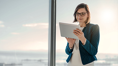 Woman in business attire using tablet while standing next to large windows.