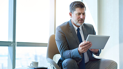 Man in business attire sitting and using a tablet.