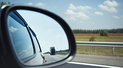 Rearview mirror displaying the large truck behind the vehicle on the road.