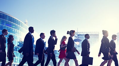 A large group of young business people crossing the street in a city