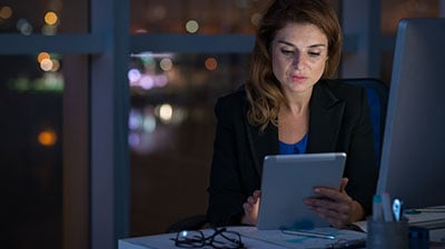 A woman using a tablet at night in the office