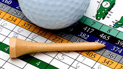 Golf-ball and tee laying on a golf scorecard