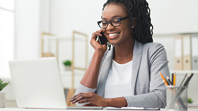 Businesswoman on phone call while using laptop at desk.