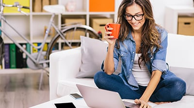 Woman sitting on couch holding coffee mug and using a laptop.