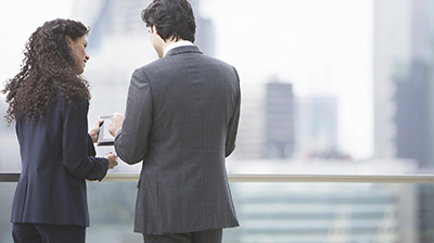 Business Woman and Business Man looking at a tablet on a rooftop
