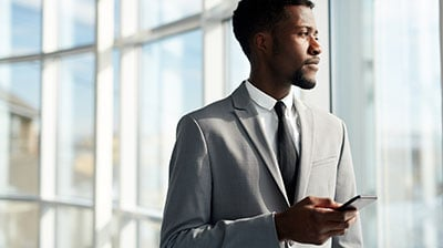 Man in business attire looking out a window while holding a cell phone in his hand.