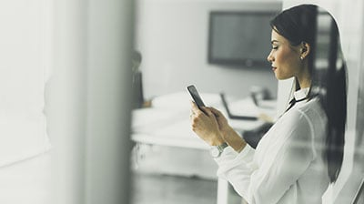 Woman in casual attire standing in an office while holding a mobile phone in front of her.