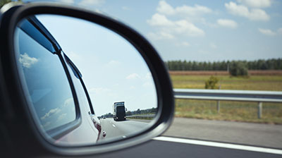 Close up of a car rear-view mirror, in the mirror you can see an large truck driving on a road.