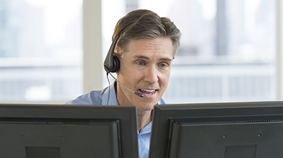 A man wearing a headset sitting at his computer