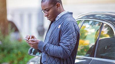 Man dressed in casual attire leaning on car door using a phone.