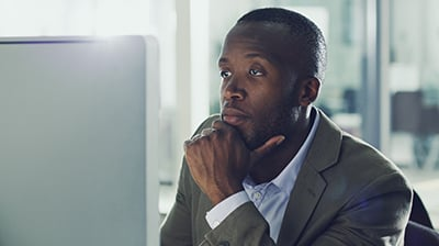 Man dressed in business casual attire looking at computer screen with his chin resting in his hand.