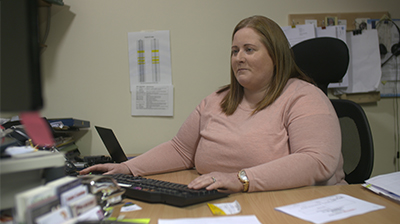 Woman in casual attire sitting behind a desk in an office, she is looking at a computer screen in front of her with her hand on a keyboard.