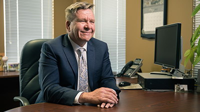 Man dressed in business attire sitting in office smiling and looking forward.