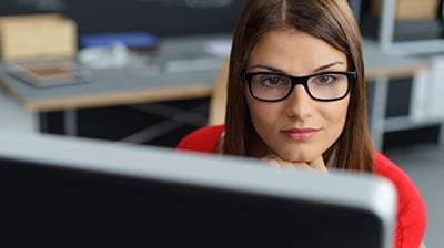 Young woman with glasses looking at computer