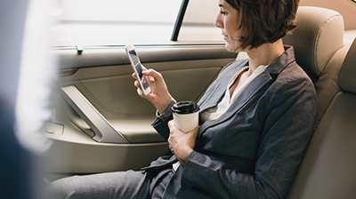 Businesswoman in car holding coffee reading her smart phone