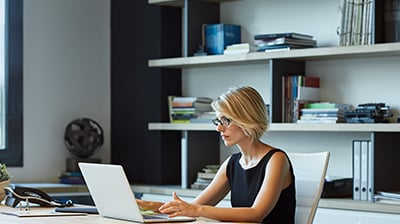 Woman seated at desk working with laptop