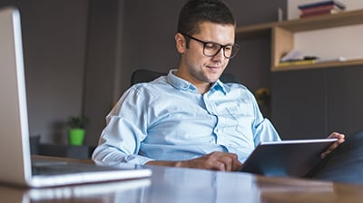 Man in business attire sitting behind a desk in an office, he is looking down at a tablet in his hands.