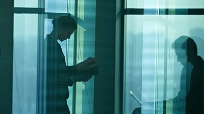 Silhouettes of two people working in the office