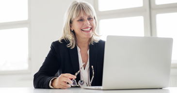 A woman in business attire sitting at a desk smiling while looking at an open laptop.