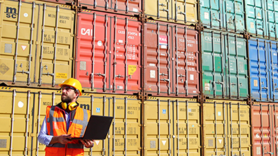 A man reviewing items on a laptop in front of shipping containers