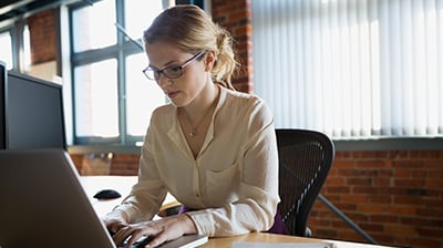 Woman in business attire sitting at desk using a laptop.
