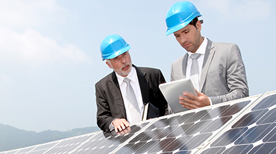 Two businessmen standing over solar panels reviewing items on a tablet
