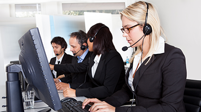 A group of customer support representatives. A young businesswoman is the focal point