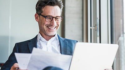 Man in business attire smiling while looking at laptop and holding documents.