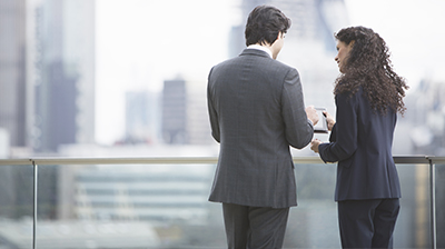 Two young business people working together on a rooftop