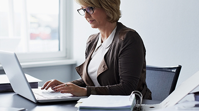 Woman in business casual attire sitting at desk using laptop.