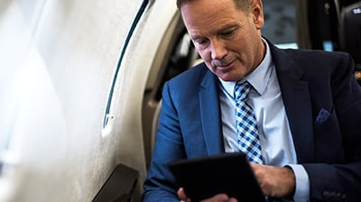 Man in business attire sitting on an airplane using a tablet.
