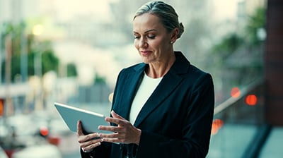 Woman in business attire standing outside using a tablet.