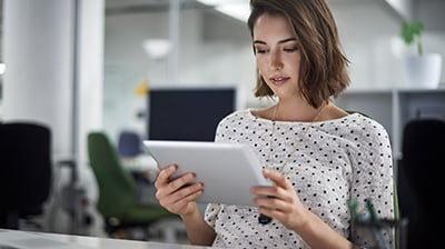 Woman in business casual attire sitting at desk using a tablet.