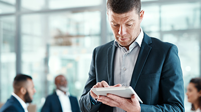 Man in business attire standing in front of colleagues conversing while he uses a tablet.