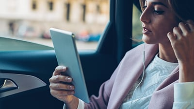 Woman in business attire sitting in car with window down using a tablet with earphones in her ears.