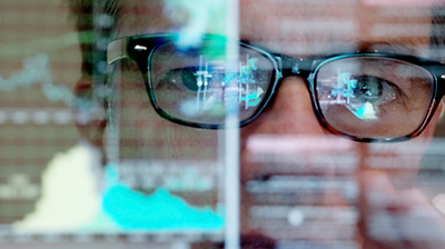 Close up image of man wearing glasses looking straight forward. The reflection of a computer screen can be seen in his glasses.