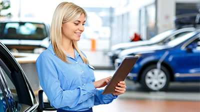 A young woman at a car dealership looking at a tablet