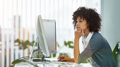 Woman in casual attire sitting at a desk in an office, she is looking at a large computer screen in front of her.