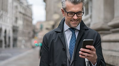 A businessman wearing glasses, standing outside, looking at his mobile phone