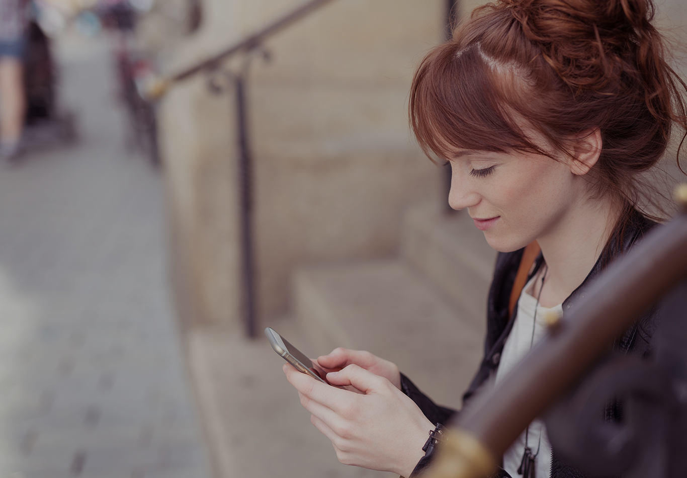 A woman is sitting on the steps looking at her phone