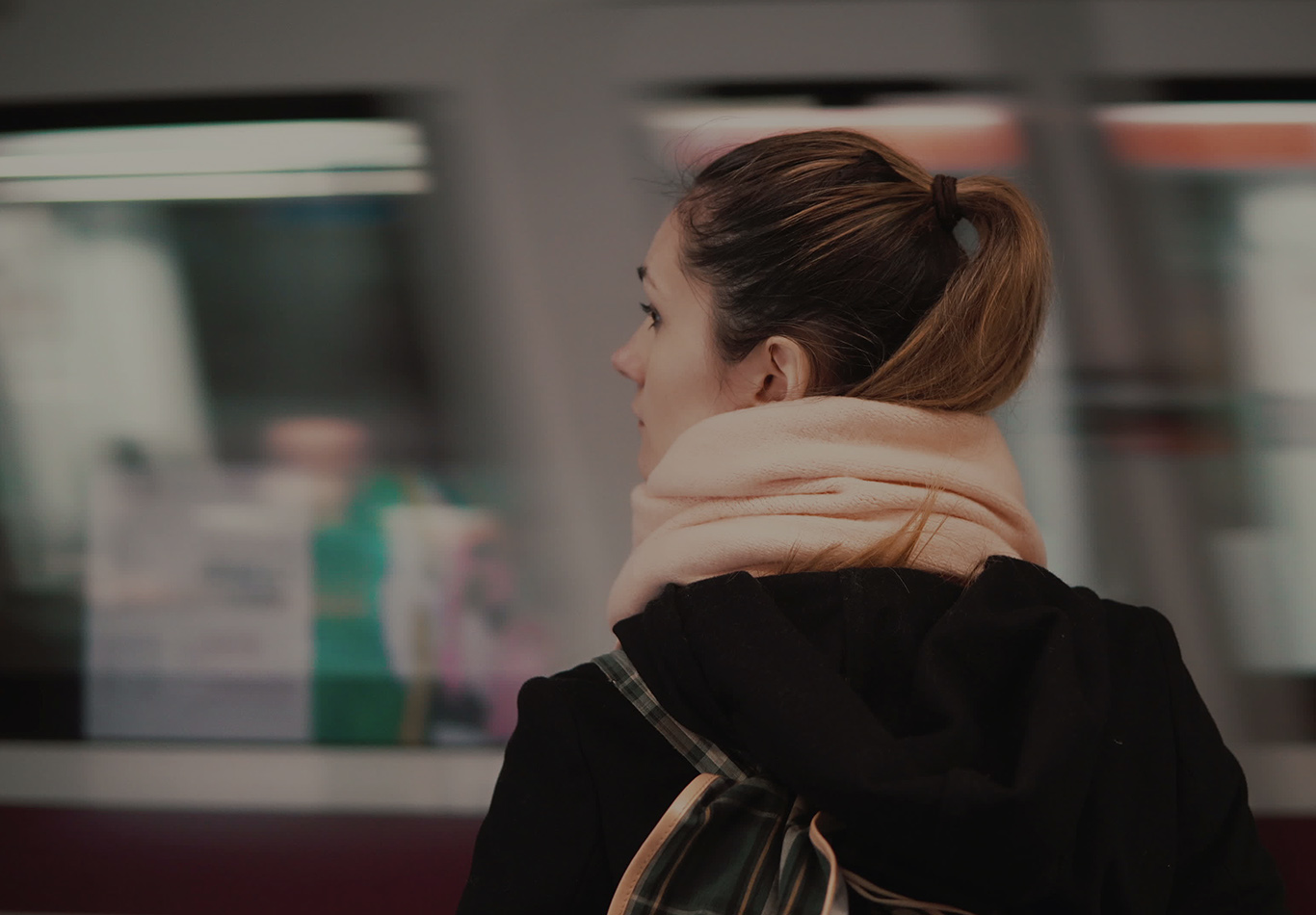 A woman is standing and looking while a train passes by