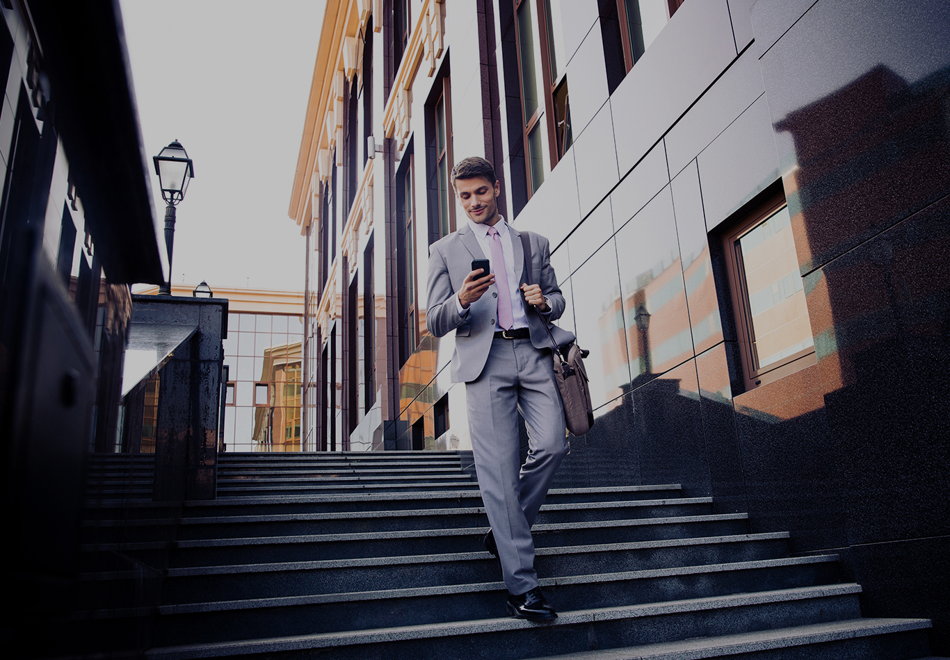 A man in a suit is walking down stairs and looking at a phone