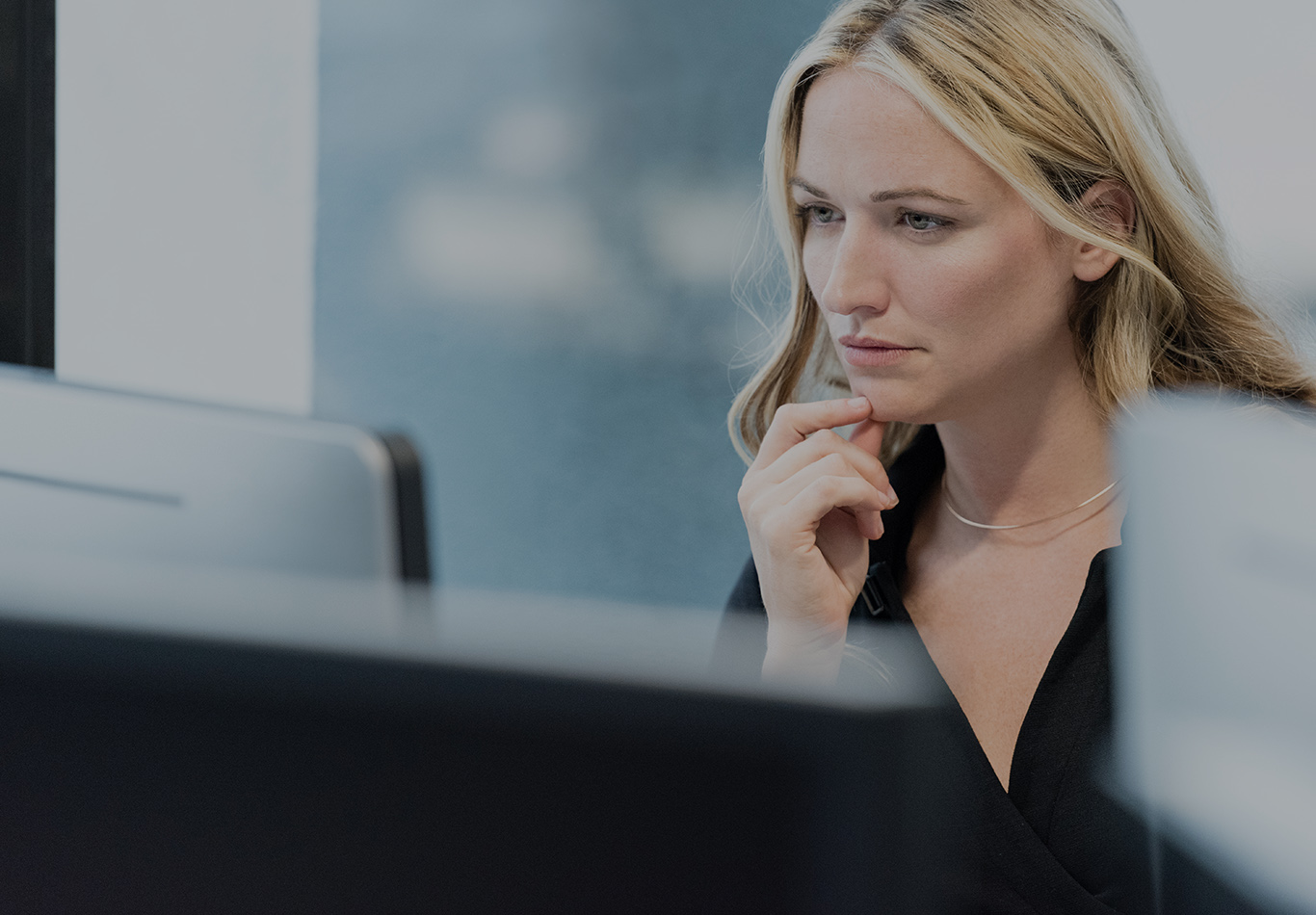 A blonde haired woman with two fingers on her chin is looking at a computer