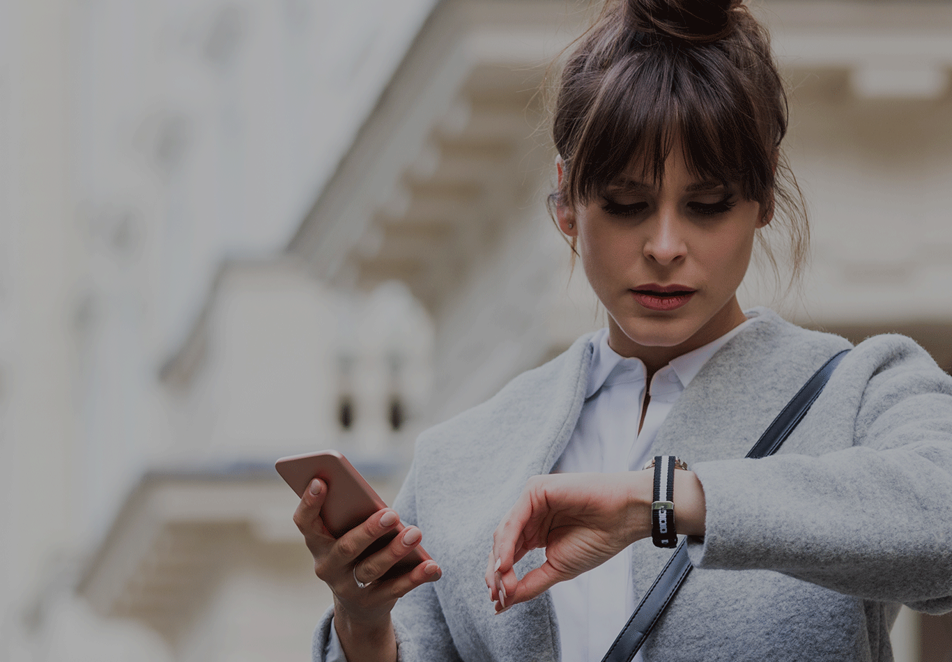 Woman in business attire looking down at watch and holding a smartphone.