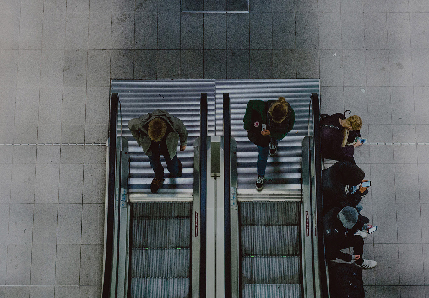 Two people are walking on to two separate escalators. Four people are sitting next to an escalator and they are on their phones