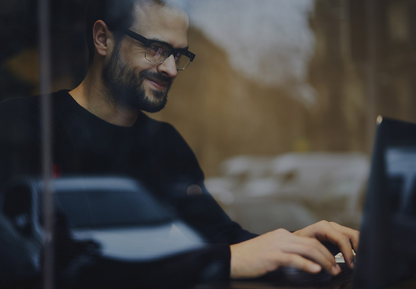 A bearded man wearing glasses is working on a laptop