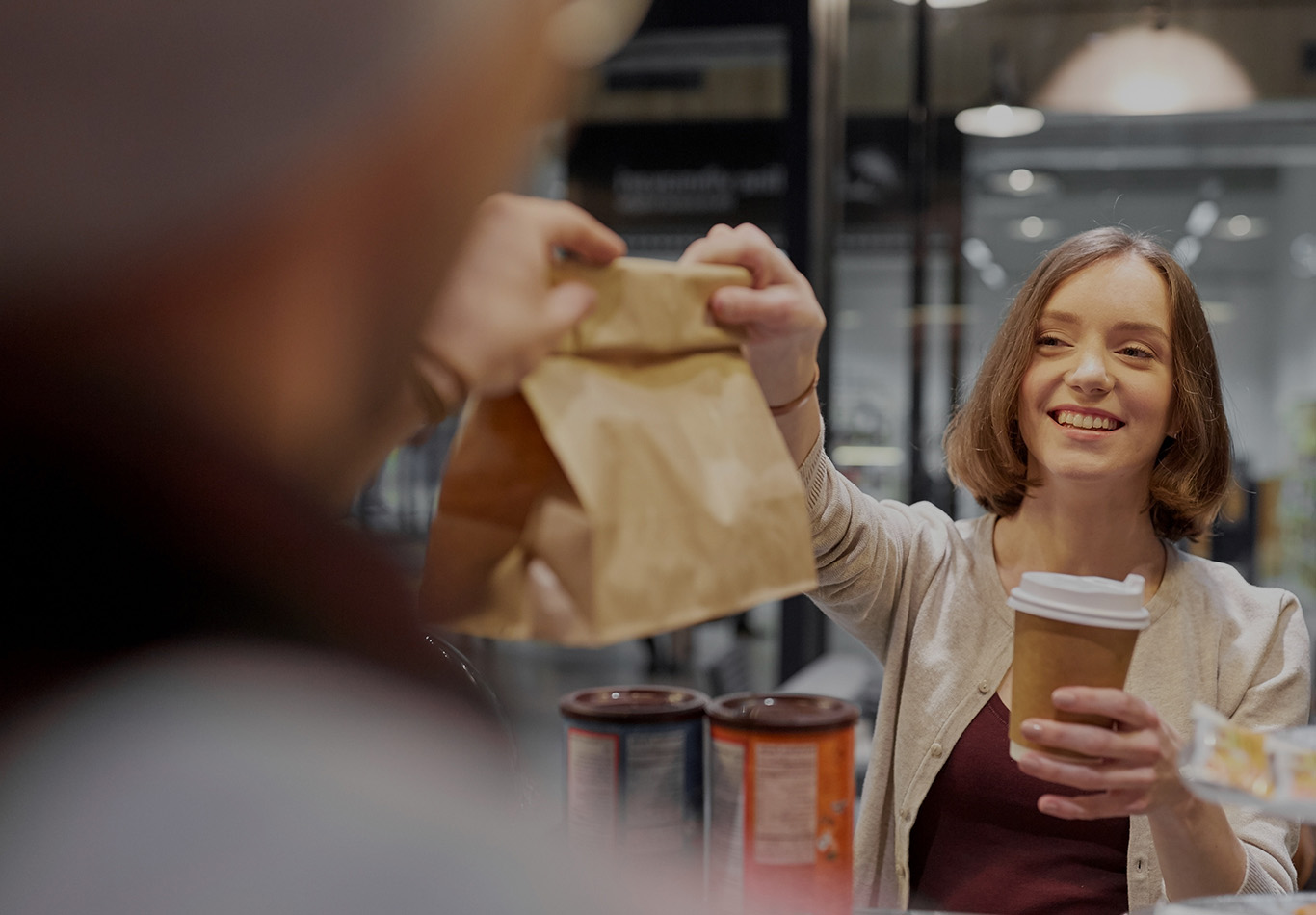 A woman holding a coffee cup is receiving a bag from another person