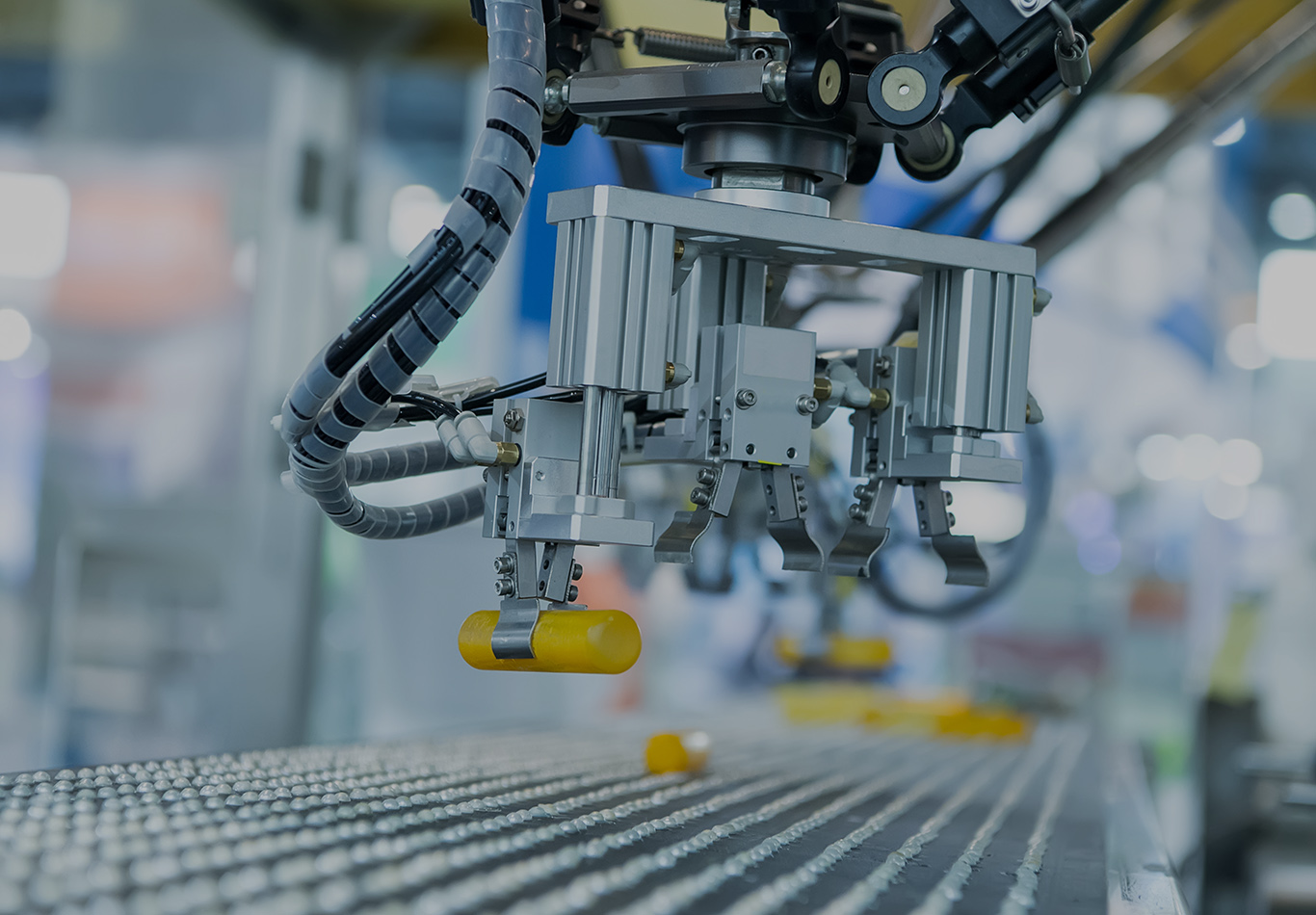 A robot on an assembly line is holding a yellow tube