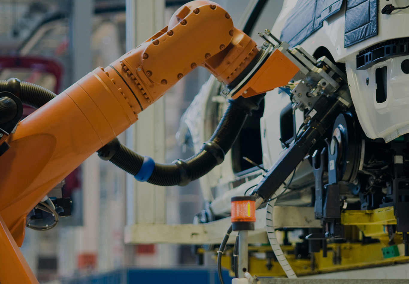 A robot arm is installing something on an automobile in an assembly line.
